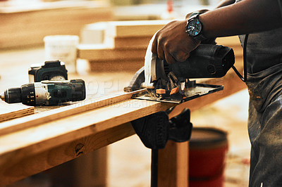 Buy stock photo Cropped shot of an unrecognizable carpenter using a circular saw to cut wood inside a workshop