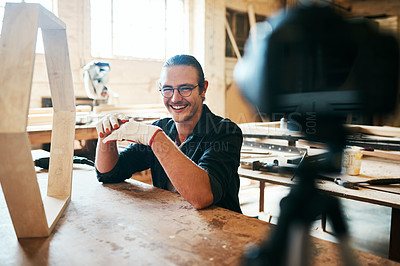 Buy stock photo Portrait of young carpenter recording a tutorial of him making a wooden masterpiece on a video camera inside his workshop