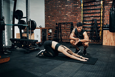 Buy stock photo Shot of a young woman working out with her personal trainer