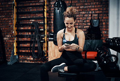 Buy stock photo Shot of a sporty young woman using a digital tablet while sitting in the gym