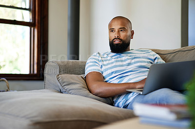 Buy stock photo Cropped shot of a handsome young man looking thoughtful while using a laptop in his living room at home