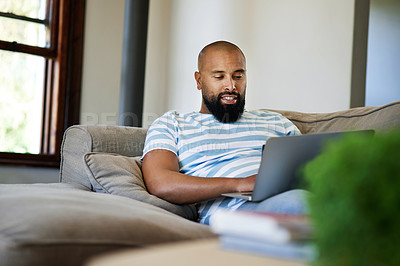 Buy stock photo Cropped shot of a handsome young man using a laptop while relaxing in his living room at home