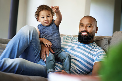 Buy stock photo Cropped shot of an adorable little boy pointing at something while spending time with his dad at home