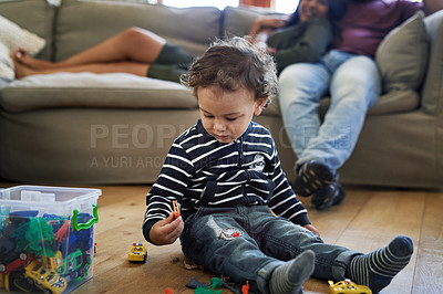 Buy stock photo Cropped shot of an adorable little boy playing with his toy cars at home with his parents in the background