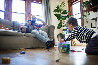 Buy stock photo Cropped shot of an affectionate young couple relaxing on a couch with their son playing with toys on the floor at home