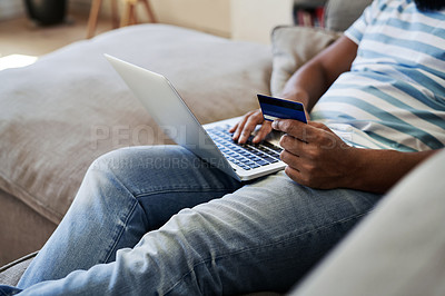 Buy stock photo Cropped shot of an unrecognizable man using a credit card and a laptop to shop online in his living room at home