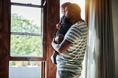 Buy stock photo Cropped shot of an affectionate young single father looking outside the window with his little son at home