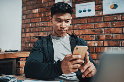 Buy stock photo Cropped shot of a handsome young male fitness instructor using a smartphone while working in a gym
