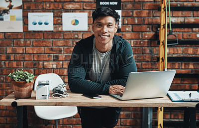 Buy stock photo Cropped portrait of a handsome young male fitness instructor using a laptop while working in a gym