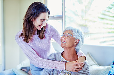 Buy stock photo Shot of a young woman spending quality time with her mother on the sofa at home