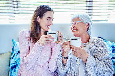 Buy stock photo Shot of a young woman enjoying a coffee break with her mother on the sofa at home