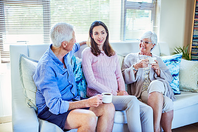 Buy stock photo Shot of a young woman enjoying a coffee break with her elderly parents on the sofa at home