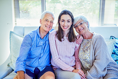 Buy stock photo Shot of a young woman spending quality time with her elderly parents on the sofa at home