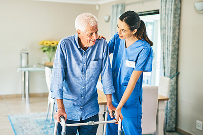 Buy stock photo Cropped shot of an attractive young female physiotherapist assisting a senior man to walk using a walker in a modern clinic