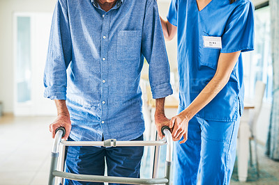 Buy stock photo Cropped shot of an unrecognizable female physiotherapist assisting a senior man to walk using a walker in a modern clinic