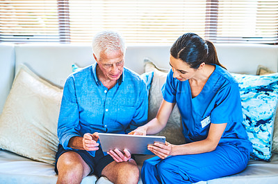 Buy stock photo Cropped shot of an attractive young female doctor and her senior patient using a digital tablet during a consultation