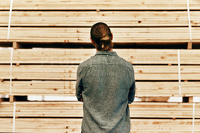 Buy stock photo Rearview shot of young carpenter looking at a piles of wood inside a workshop