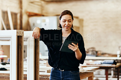 Buy stock photo Shot of a young female carpenter using a digital tablet while working inside her workshop