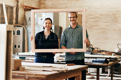 Buy stock photo Portrait of two young carpenters holding a wooden frame together inside their workshop