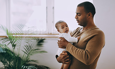 Buy stock photo Shot of a young man bonding with his adorable baby boy at home