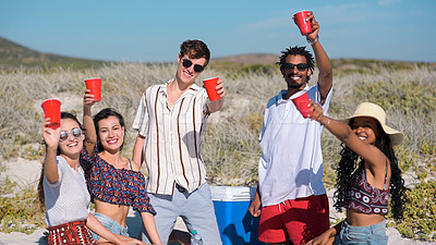 Buy stock photo Portrait of a group of young people raising their cups for a toast while enjoying themselves at the beach