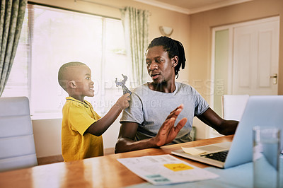 Buy stock photo Cropped shot of an adorable little boy trying to be playful with his father at home
