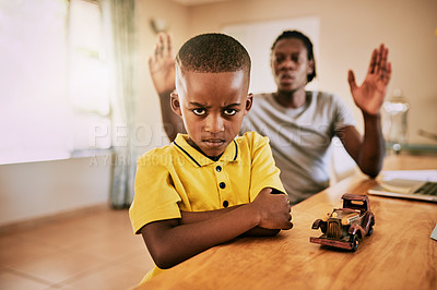 Buy stock photo Cropped shot of a little boy looking upset while his father is talking to him in the background