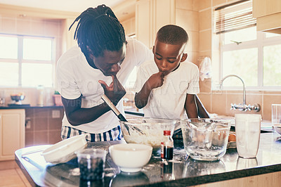 Buy stock photo Cropped shot of a playful father and son tasting their pancake batter in their kitchen at home