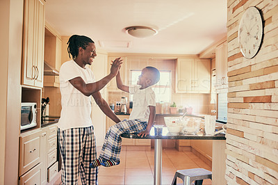 Buy stock photo Cropped shot of a handsome young man standing and giving his son a high five while making breakfast at home
