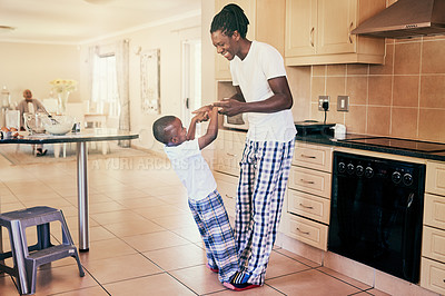 Buy stock photo Full length shot of a happy young boy standing on his father's toes during a dance in their kitchen