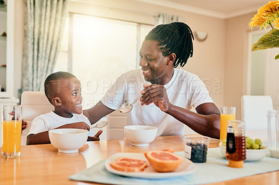 Buy stock photo Cropped shot of a happy father and son bonding over breakfast during a weekend at home