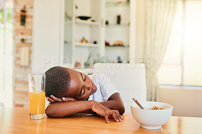 Buy stock photo Cropped shot of an adorable young boy asleep at the table after eating breakfast at home