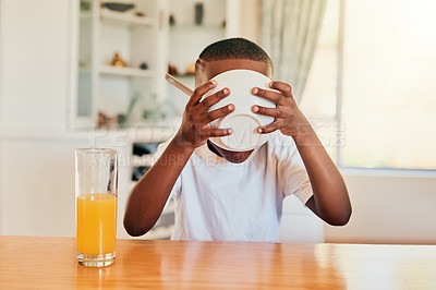 Buy stock photo Cropped shot of a happy young boy eating his cereal for breakfast while sitting alone at the table
