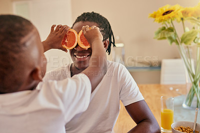 Buy stock photo Cropped shot of an affectionate father and son feeling playful during breakfast at home together