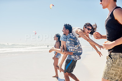 Buy stock photo Shot of four young friends enjoying themselves at the beach