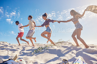 Buy stock photo Shot of a group of friends enjoying a summer's day on the beach