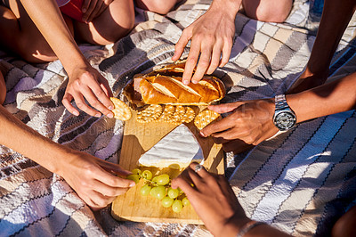 Buy stock photo High angle shot of a group of unrecognizable friends having a picnic together on the beach