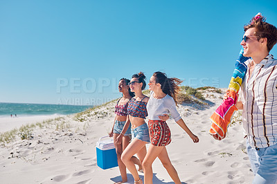 Buy stock photo Shot of a group of young friends heading out to have a picnic together at the beach