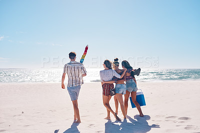 Buy stock photo Rearview shot of a group of young friends heading out to have a picnic together at the beach
