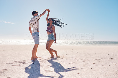 Buy stock photo Full length shot of a happy young couple dancing together on the beach