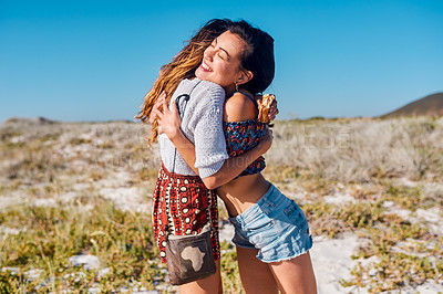 Buy stock photo Shot of two attractive young friends hugging each other outdoors on the beach