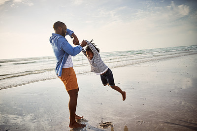 Buy stock photo Shot of a young man spending time at the beach with his adorable daughter.