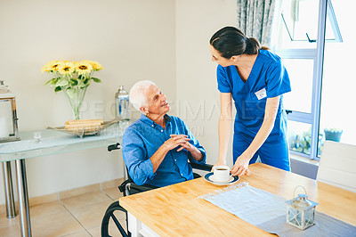 Buy stock photo Cropped shot of an attractive young female nurse serving a senior man some tea at a nursing home