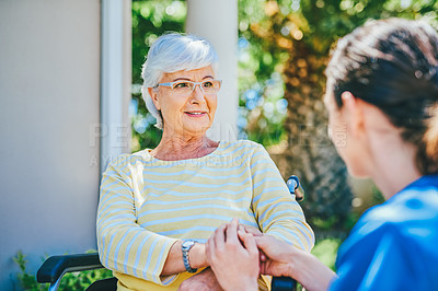 Buy stock photo Cropped shot of a senior woman looking cheerful while having a chat with a female nurse outdoors at a nursing home