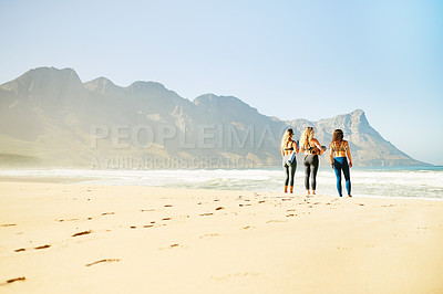 Buy stock photo Rearview shot of three young woman looking for a spot on the beach to practice yoga