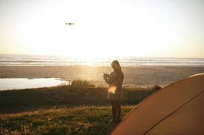 Buy stock photo Full length shot of an unrecognizable young woman flying a drone while camping outdoors by herself near the beach