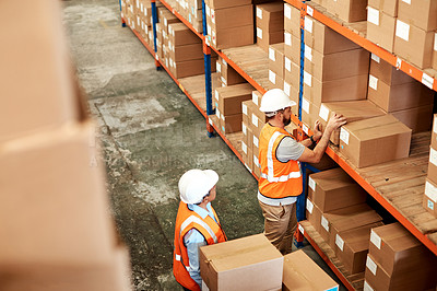 Buy stock photo High angle shot of two men working in a warehouse