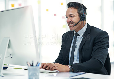 Buy stock photo Shot of a mature businessman using a headset while working on a computer in an office