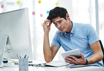 Buy stock photo Shot of a young businessman looking confused while working in an office