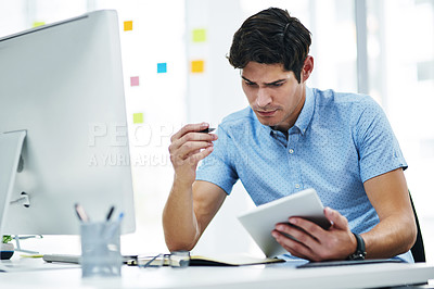 Buy stock photo Shot of a young businessman writing notes while using a digital tablet and computer in an office